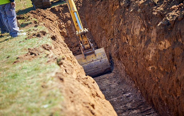 "<img src=""excavation.jpg"" alt=""excavator digging trench in grass field"">"