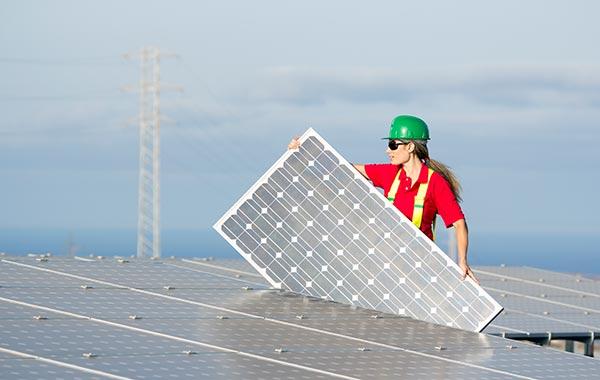 Female contractor installing solar panel