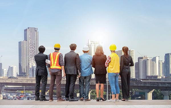 Team of professionals in suits and construction clothes staring at a city skyline