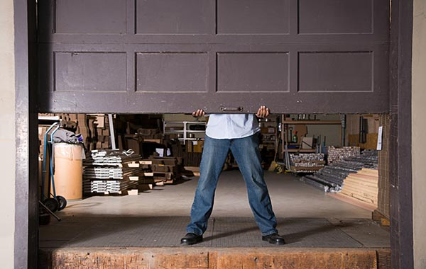 Man lifting up brown garage door that leads to construction supplies